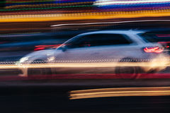 White Compact Car in a Blurred City Scene Royalty Free Stock Photography