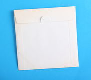White Compact Disc Envelope. Old and stained blank white paper envelope used to store a compact disc on a plain blue paper background, with copy space stock photography