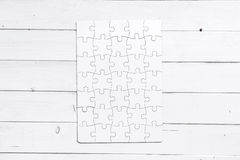 White completed puzzle on white wooden table Royalty Free Stock Image