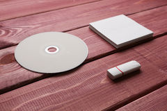 White composition. White CD and phone and white paper lying on a wooden table Royalty Free Stock Images