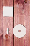 White composition. White CD and USB-flash and white paper lying on a wooden table Stock Photo