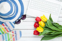 White computer and flip flops shoes with tulips Royalty Free Stock Photo