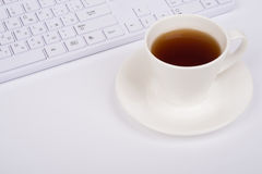 White computer keyboard and coffee cup, top view Royalty Free Stock Photo