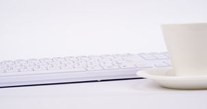 White computer keyboard and cup Royalty Free Stock Photography