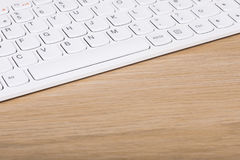 White computer keyboard on a wooden desk Stock Photos