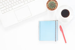 White computer laptop with coffee cup, notebook and cactus Royalty Free Stock Photo