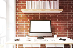 White computer screen against brick wall, front. Front view of a white computer monitor is standing on a dark wooden desk near a brick wall. There is a bookshelf Royalty Free Stock Image