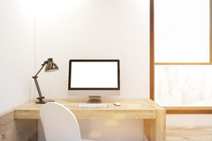 White computer screen on wooden desk, toned. White computer screen is standing on a wooden desk in an office with white walls and a large window. 3d rendering Royalty Free Stock Photos