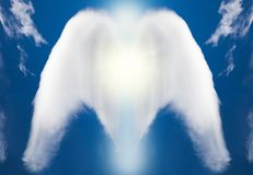 White concept of angel made by clouds on sky. Beautiful abstract shape of an white angel drawing concept with clouds on blue sky Stock Photos