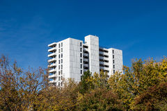 White Concrete Apartment Building. A white concrete apartment or condo building rising from the trees in Denver, Colorado Stock Image