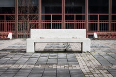 Concrete bench with nobody around. White concrete bench with nobody around and architectural background Royalty Free Stock Photography