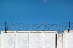 White concrete fence with barbed wire against a blue sky. Background Stock Image