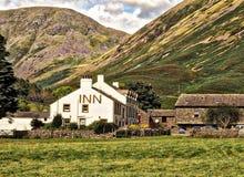 White Concrete Inn Near Green Covered Mountain at Daytime Royalty Free Stock Photo