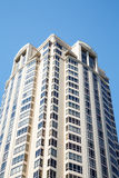 White Condo Tower Under Blue Skies. A modern white condominium tower under clear blue skies Royalty Free Stock Photography