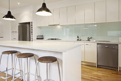 White contemporary kitchen with island. And bar stools Stock Photo