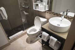 Modern bathroom sink and toilet and staning shower with glass shower doors stock photography