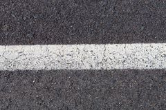 White continuous line on a grey road. View of a road with a white line royalty free stock photos