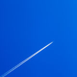 White contrail trace of plane on blue sky. Royalty Free Stock Photos