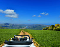 White convertible on a country road through fields Stock Images