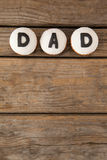 White cookies with black dad text on table. Overhead view of white cookies with black dad text on wooden table Royalty Free Stock Photos