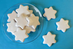 White cookies in the shape of stars on the transparent saucer and on blue background Royalty Free Stock Image