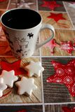 White cookies stars and cup decorated with elks on festive tablecloth with stars and wooden pattern. Stock Images