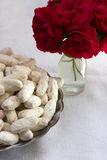 White cookies and vase with red roses. White cookies  on a white tablecloth background, next to a vase with red roses Royalty Free Stock Photography