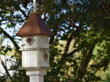 Pole mounted white bird house with copper roof Royalty Free Stock Photography