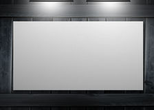 White copy space poster hung on a wall. And lighted with spotlights Royalty Free Stock Photos