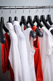White and coral womens clothing hanging vertical Stock Photo