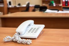 White corded telephone standing on office desk, empty room. White corded telephone standing on wooden office desk, empty room Stock Image