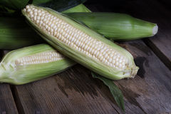 White Corn Wood Surface. Several ears of white corn, two open and trimmed on rustic wood surface Stock Photo