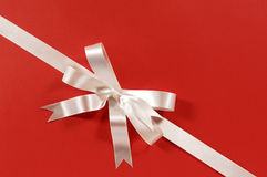 White corner diagonal gift ribbon bow on red paper background Royalty Free Stock Image