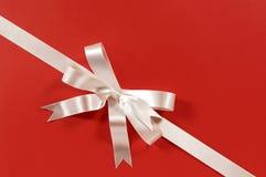 White corner diagonal gift ribbon bow on red paper background. Diagonal gift ribbon and bow in white satin on red paper background Royalty Free Stock Image