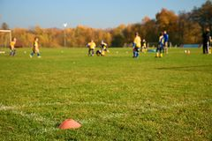 White corner line on green football field. Small boys are playing match.  Plastic cone. Royalty Free Stock Images