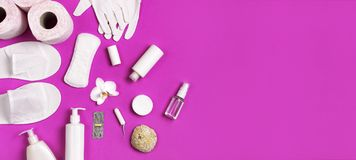 White cosmetic bottle containers gloves slippers hygiene items gasket tampon cotton pads toilet paper tablet orchid flower on pink. Background top view flat lay stock photography