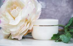 White cosmetic container on white, decorated with a large flower Royalty Free Stock Image