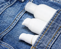White cosmetic containers in blue jeans pocket Stock Images