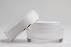 White cosmetic cream jar. White glass cosmetic cream jar and open lid Royalty Free Stock Image