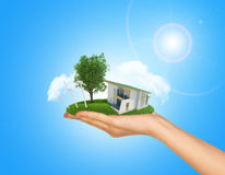 White cottage in hand with green roof. Background Stock Photography