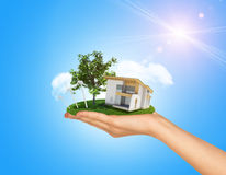 White cottage in hand with green roof. Background Stock Image