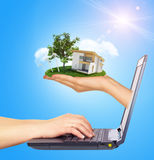 White cottage in hand with green roof of screen Stock Photo