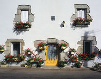 White cottage with hanging baskets, Brittany, France Stock Photography