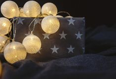 White cotton ball light garland in a grey basket with stars sparkling at home. close up, bright lights, festive atmosphere stock photo
