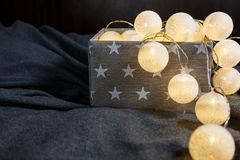 White cotton ball light garland in a grey basket with stars sparkling at home. close up, bright lights, festive atmosphere stock photos