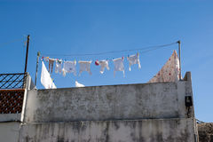 White cotton linen cloth hanging outside on a balcony. White cloth hanging outside to dry on a balcony during a sunny day with blue sky Stock Photography