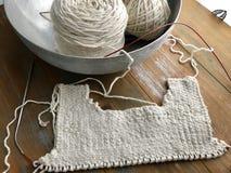Knitting work in progress. White cotton yarn linen stitch baby dress work in progress. Ivory cotton yarn in metal stock photography