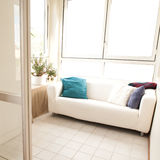 White couch in a small bright room Royalty Free Stock Photography