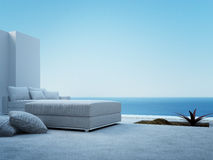 White couch standing on a patio with seascape view Royalty Free Stock Images