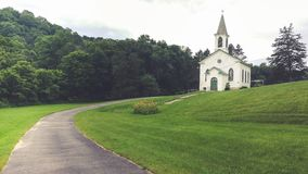 White Country Church on a Grassy Hillside stock photo